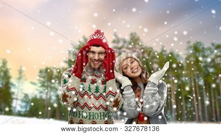 christmas, clothes and holidays concept - portrait of happy couple in ugly sweaters over winter park background