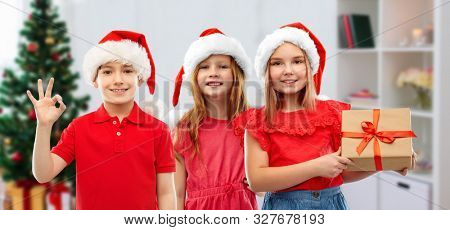 christmas, holidays and childhood concept - smiling little children in santa helper hats with gift box showing ok hand sign over home background