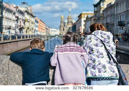 Tourist Family With Mother, Doughter And Son Walk And See The Sights In Famous Place In Saint Peterb