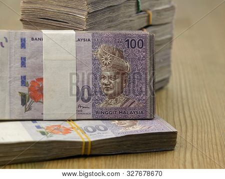 bundles of malaysia currency on the wooden table