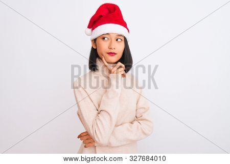 Young beautiful chinese woman wearing Christmas Santa hat over isolated white background with hand on chin thinking about question, pensive expression. Smiling with thoughtful face. Doubt concept.