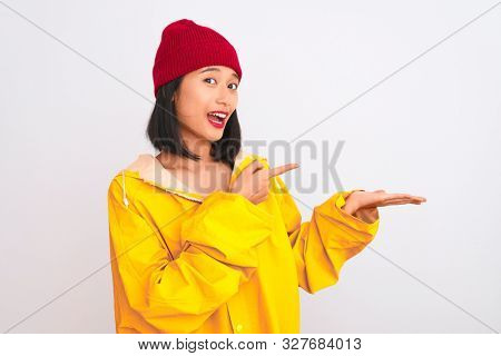 Young beautiful chinese woman wearing raincoat and wool cap over isolated white background amazed and smiling to the camera while presenting with hand and pointing with finger.