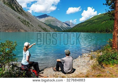 Young Tourists With Backpacks On The Lake Shore Enjoy A View Of The Mountain Range.