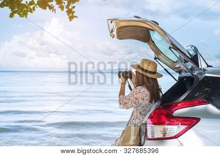 Young Woman Traveler Taking A Photo At The Beach With Car On Roadtrip, Summer Vacation