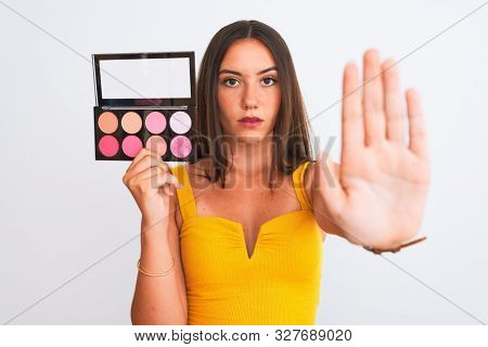 Young beautiful girl holding makeup standing over isolated white background with open hand doing stop sign with serious and confident expression, defense gesture
