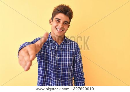 Young handsome man wearing casual shirt standing over isolated yellow background smiling friendly offering handshake as greeting and welcoming. Successful business.