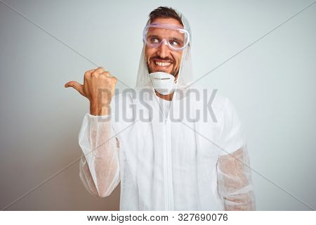 Painter man wearing professional worker equipment protection over isolated background smiling with happy face looking and pointing to the side with thumb up.