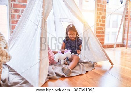 Beautiful toddler girl sitting on the floor playing with unicorn inside tipi at kindergarten