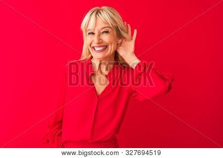 Middle age woman wearing elegant shirt standing over isolated red background smiling with hand over ear listening an hearing to rumor or gossip. Deafness concept.