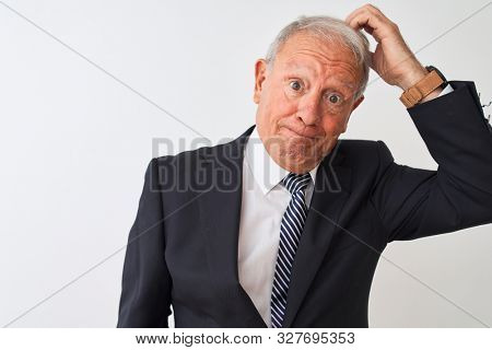 Senior grey-haired businessman wearing suit standing over isolated white background confuse and wonder about question. Uncertain with doubt, thinking with hand on head. Pensive concept.