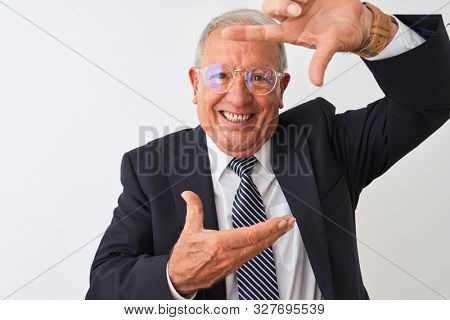 Senior grey-haired businessman wearing suit and glasses over isolated white background smiling making frame with hands and fingers with happy face. Creativity and photography concept.