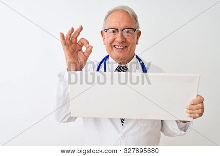 Senior grey-haired doctor man holding banner standing over isolated white background doing ok sign with fingers, excellent symbol