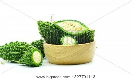 Fresh Bitter Gourd With Half Sliced In Wood Bowl On White Background, Closeup View Of Bitter Melon.