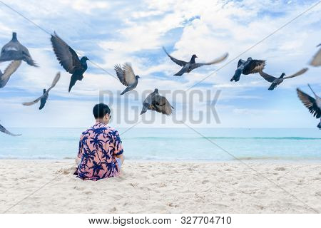 A Young Man Sitting On The Beach With Flying Pigeons