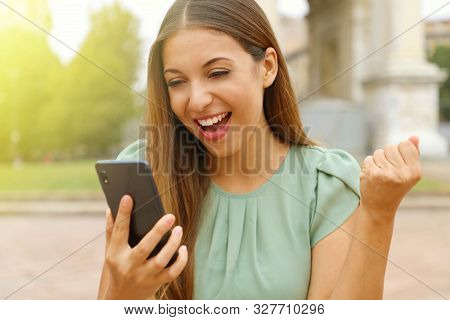 Brazilian Exuberant Business Woman Cheering At Good News On Her Mobile Phone And Punching The Air Wi