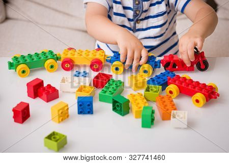 Toddler Child Playing Multi-colored Cubes On The Table. Colorful Plastic Bricks For The Early Develo
