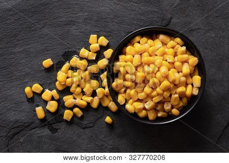 Canned Sweet Corn In A Black Ceramic Bowl Isolated On Black Slate Next To Spilled Sweet Corn. Top Vi