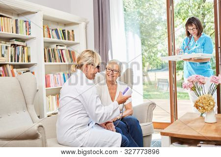 The doctor and the geriatric nurse look after a senior woman in the senior citizen residence