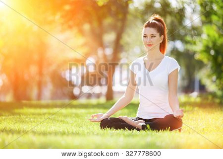 Yoga outdoor. Happy woman doing yoga exercises, meditate in sunny park. Yoga meditation in nature. Concept of healthy lifestyle and relaxation. Pretty woman practicing yoga on grass
