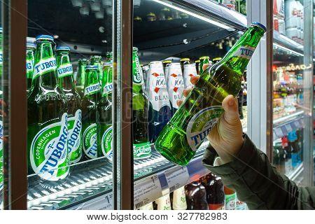 Minsk, Belarus - October 4, 2019: Buyer Takes Tuborg Beer In Refrigerator Of Supermarket. Hand Is Ho