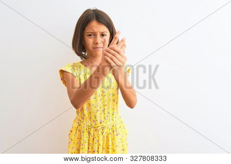 Young beautiful child girl wearing yellow floral dress standing over isolated white background Suffering pain on hands and fingers, arthritis inflammation