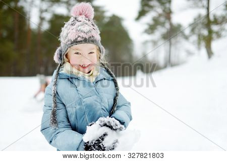 Adorable Young Girl Having Fun In Beautiful Winter Park. Cute Child Playing In A Snow. Winter Activi