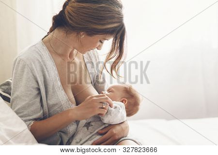 Loving mom breastfeeding her newborn baby. Bright portrait of happy mum holding infant child on arms. Mother feeding her 2 months old son by breast milk.