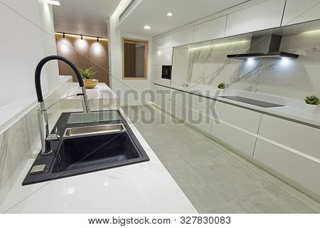 Interior design decor showing modern kitchen with cupboards and island in luxury apartment showroom poster