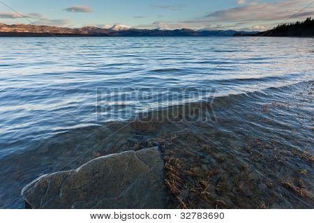 Distant snowy mountain range behind Lake Laberge