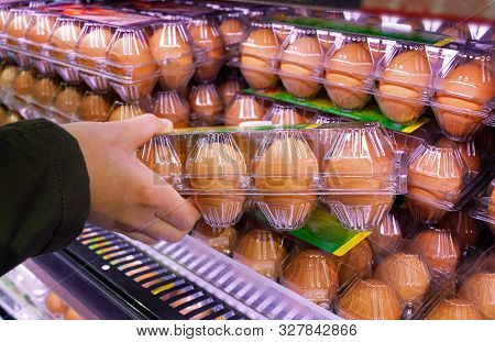 Buying Eggs In A Supermarket. Buyer Holds In His Hand A Package Of Raw Chicken Eggs.