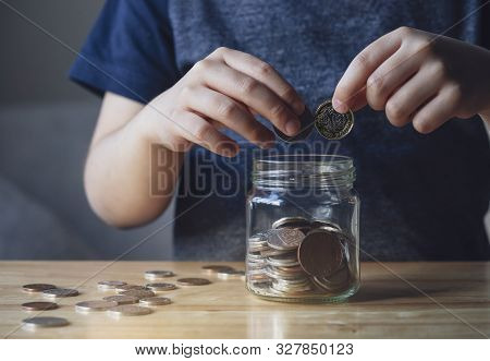 Cropped Shot Kid Hand Putting Money Coins Into Clear Jar,  Child Counting His Saved Coins, Childhood