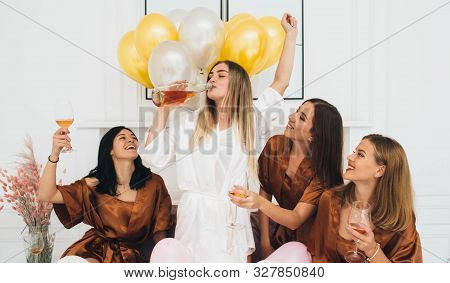 Girlfriends Wearing Satin Robes Celebrating Hen Party . Bride Drinking Alcohol And Having Fun With H