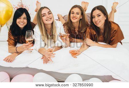 Hen Party. Beautiful Charming Women Wearing In Satin Robe Drinking Alcohol And Enjoying Pajamas Part