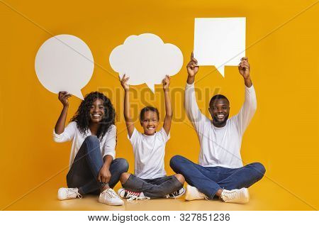 Diverse Thoughts. Happy African American Family Of Three Holding Empty Speech Bubbles Over Heads Sit