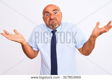 Middle age businessman wearing tie standing over isolated white background clueless and confused expression with arms and hands raised. Doubt concept.