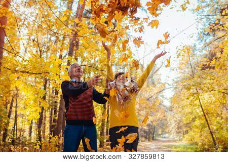 Fall Season. Couple Throwing Leaves In Autumn Forest. Senior Family Having Fun Outdoors