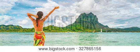Happy Tahiti tourist travel woman enjoying freedom vacation in paradise. French Polynesia hula dancer dancing on Bora Bora beach in front of Mt Otemanu, Tahiti, French Polynesia. Banner panorama.
