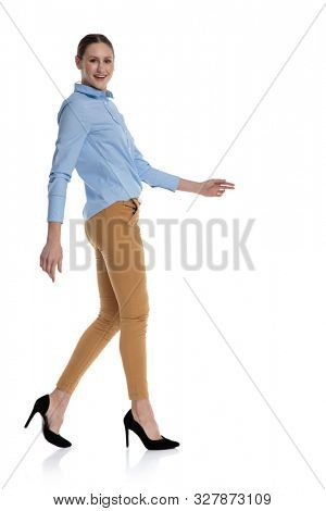 sie view of young businesswoman wearing blue shirt, smiling and walking isolated on white background