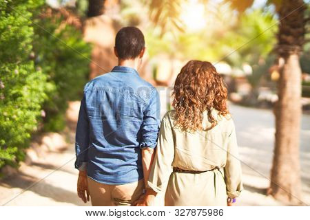 Middle age beautiful couple smiling happy and confident at town park. Walking with smile on face on backview