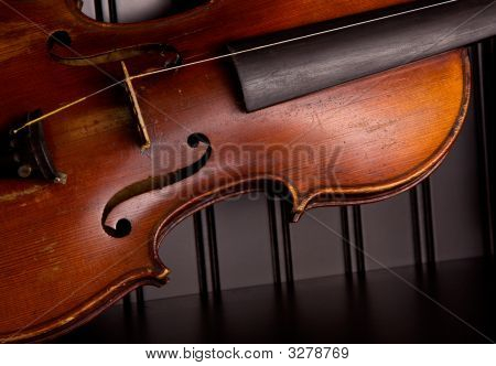 An old distressed violin with one string leaning against black beadboard wall poster