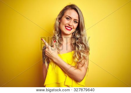 Young attactive woman wearing t-shirt standing over yellow isolated background cheerful with a smile of face pointing with hand and finger up to the side with happy and natural expression on face