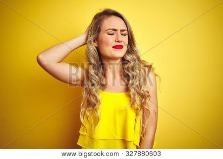 Young attactive woman wearing t-shirt standing over yellow isolated background confuse and wonder about question. Uncertain with doubt, thinking with hand on head. Pensive concept.