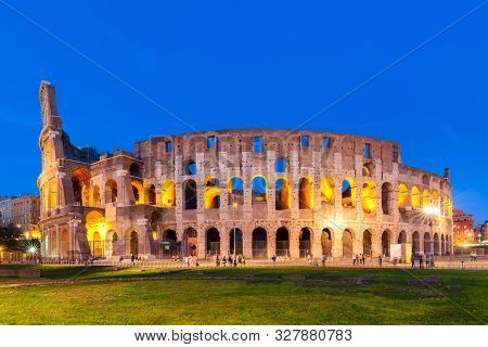 The Colosseum In Rome, Italy At Sunset Twilight. Blue Hour Photo In The Evening. The World Famous Co