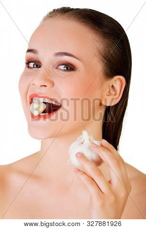 Woman holding garlic in mouth to eat them. Natural cure for flu or cold.