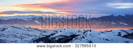 Gorgeous Panorama Of Mountainous Countryside At Sunrise In Winter. Snow Covered Rural Area On Rollin