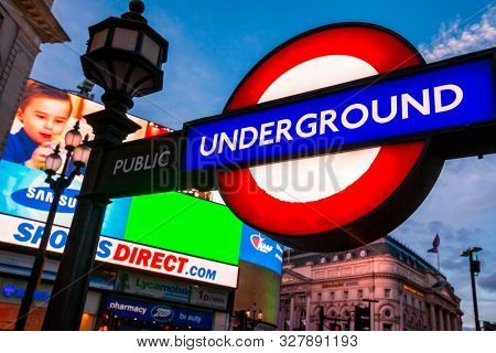 LONDON, UK - JUNE 16, 2013: Illuminated London Underground Tube sign at Piccadilly Circus station entrance with LED video advertising display in background