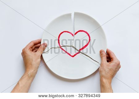 Top View Of Man Hands Holding A Broken White Plate With Heart Symbol. Love Is Gone. Isolated On Whit