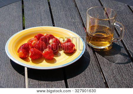 Red Berries Of Garden Strawberries With Green Sepals On A Sunny Yellow Porcelain Plate On A Dark Rou