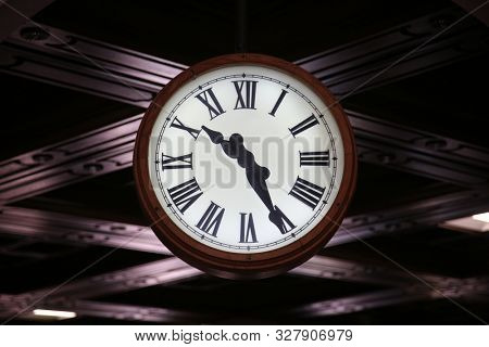 Clock. A large clock read the time as 10:26 am or pm. Large Analog Time Clock with Roman Numerals.