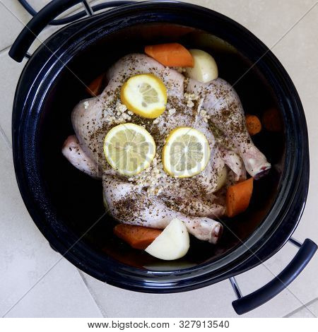 Fresh Chicken And Vegetables With Herbs And Lemon Slices In A Slow Cooker.